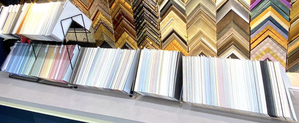 Matboard selections that we offer for custom framing on the counter in front of corner moulding samples.