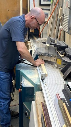 Giovanni uses the Prisma Miter Saw to cut the wood frame before stretching a canvas.